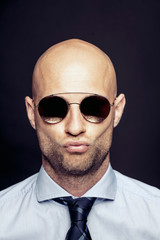 Portrait of bald businessman wearing mirrored sunglasses pouting mouth