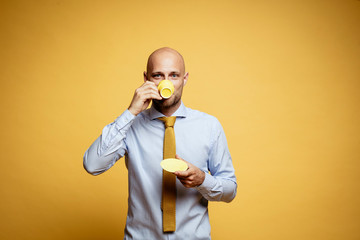 Portrait of bald businessman drinking cup of coffee against yellow background