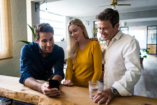 Smiling business team looking at cell phone together in loft office