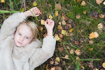 Portrait of blond girl lying on a meadow in autumn, top view