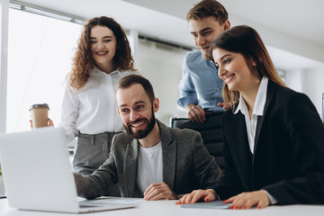 Beautiful business people are using computers and smiling while working in office