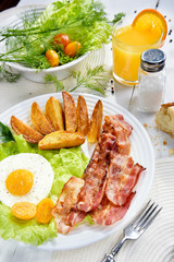 Food on the table. Breakfast with bacon. Fried bacon with. French fries and tender egg, and a glass of fresh juice.