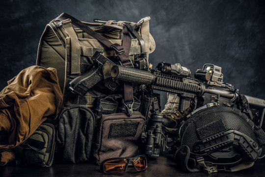 Military uniform and equipment. Body armor, gun, assault rifle, helmet, night vision goggles. Studio photo against a dark textured wall