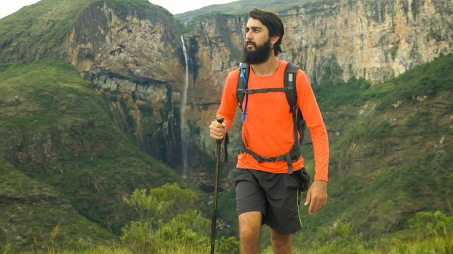 Man climbing hill walking stick in hand and backpack, Waterfall of Tabuleiro in the background