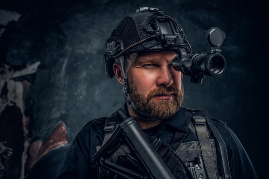Close-up portrait of a bearded special forces soldier observes the surroundings in night vision goggles. Studio photo against a dark textured wall
