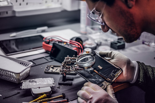 The technician uses a magnifying glass to carefully inspect the internal parts of the smartphone in a modern repair shop