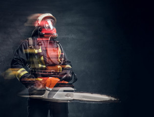 Firefighter in safety helmet and oxygen mask holding a chainsaw. Studio photo with light effects against a dark textured wall
