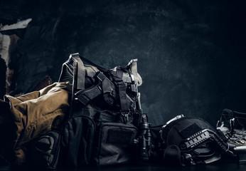 Military uniform and equipment. Body armor, gun, helmet, night vision goggles, boots. Studio photo against a dark textured wall