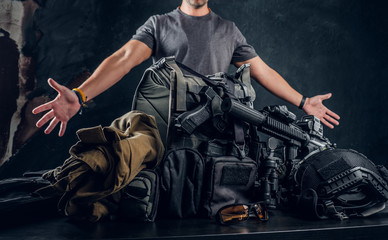 Casually dressed man showing his military uniform and equipment. Modern special forces equipment. Studio photo against a dark textured wall