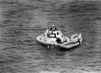 The Apollo 9 crew awaits the arrival of a recovery helicopter after splashdown