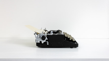 Old retro vintage black typewriter in black laid on white desk in front of white wall with paper and copy space