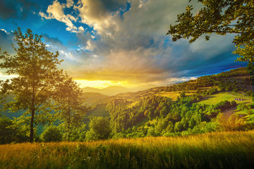 Colorful sunset over the green hills landscape