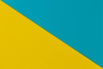 Wall Mural - Vibrant yellow and sky blue colored plastic surfaces jointed diagonally, background.