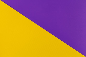 Wall Mural - Vibrant yellow and purple colored plastic surfaces jointed diagonally, background.
