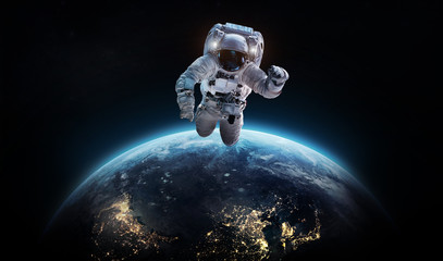 Wall Murals Nasa Astronaut in the dark space near the planet Earth. NIghtly Earth. City lights. Spaceman. Elements of this image furnished by NASA