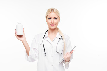 Attractive young female doctor with stethoscope pointing at white pill bottle isolated on white background