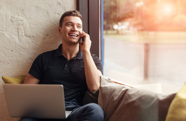 Laughing man with laptop speaking on phone
