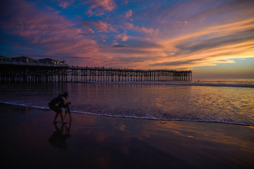 Photographer taking photo of a sunset at the pier