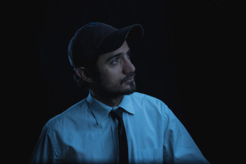 portrait with black background of a young man in cap shirt and tie