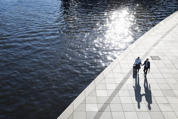 Two businessmen walking and talking at the riverbank