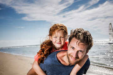 Netherlands, Zandvoort, portrait of smiling father carrying daughter on the beach