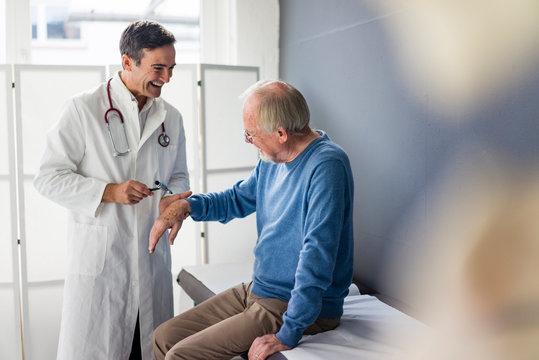 Happy doctor examining senior patient in medical practice