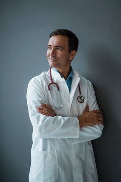 Smiling doctor standing at a grey wall looking sideways