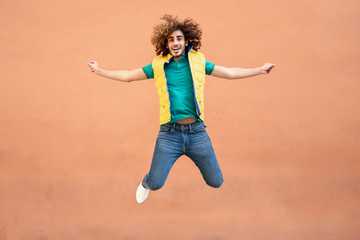 Portrait of smiling young man with curly hair wearing yellow waistcoat jumping in the air