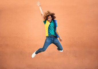 Happy young man with curly hair wearing waistcoat jumping in the air