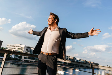 Happy businessman standing on balcony, with arms out