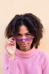 Portrait of young woman wearing pink turtleneck pullover and purple sunglasses