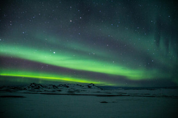Winter scenic landscape night view of  Aurora Borealis/Northern lights dancing on the clear sky full of stars above snow covered mountains. Mývatn, North Iceland. Beautiful winter background scene.