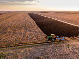 Serbia, Vojvodina. Tractor plowing field in the evening