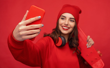 Hipster girl in red clothes taking selfie