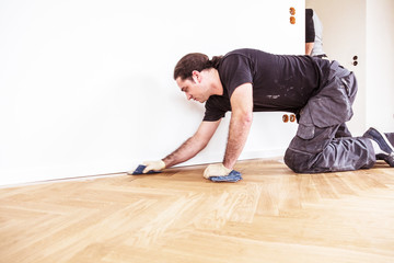 Obraz Male hand cleaning and rubbing an hardwood floor with a microfiber cloth - fototapety do salonu