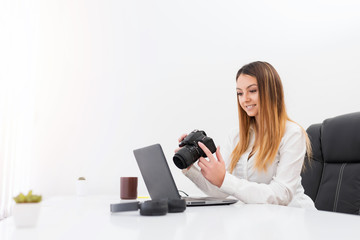 Cheerful freelance photographer woman, at home office editing photos.