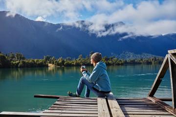 Chile, Chaiten, Lago Rosselot, woman sitting on jetty holding mug