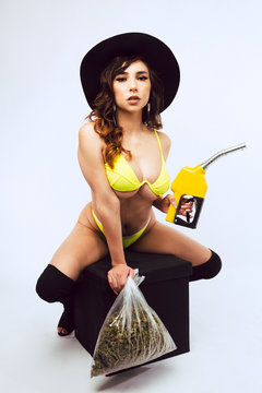Mixed race woman in yellow bikini poses with bag of cannabis and diesel fuel pump