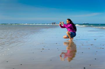 Denmark, Jutland, Skagen, Grenen, woman taking pictures of North Sea and Baltic Sea