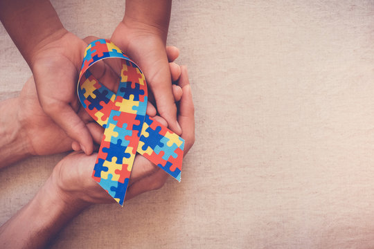 Hands holding puzzle ribbon, World Autism Awareness Day, Autism spectrum  disorder