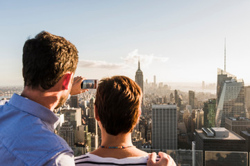 USA, New York City, man with woman taking cell phone picture on Rockefeller Center observation deck
