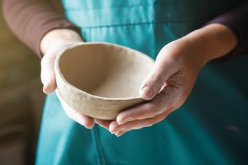 Obraz pottery making, hands holding ceramic bowl - fototapety do salonu