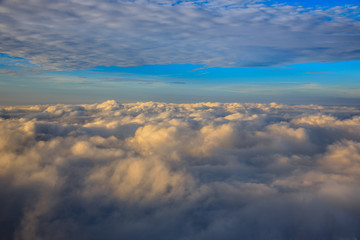 Abstract photograph above the clouds, sea of clouds effect, flying through the sky, aerial view, white puffy clouds and blue sky. Low pressure front atmospheric effect, cloudscape, clear weather.