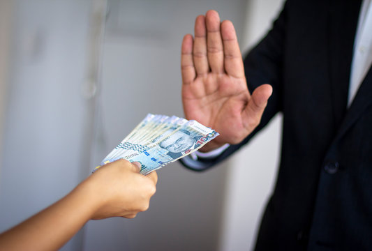 Official rejecting money offered by a woman, Peruvian soles currency in notes of 100 bills. Anti bribery and corruption concepts.