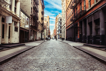 New York City old SoHo Downtown paving stone street with retail stores and luxury apartments Fotobehang