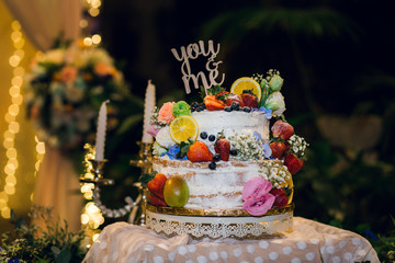 Wedding cake decorated with berry, strawberry, orange and you and me text