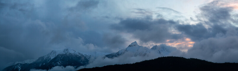 Striking and Dramatic Panoramic Canadian Landscape View of the Mountain Peaks during a cloudy sunset. Taken in Tantalus Lookout near Squamish and Whistler, North of Vancouver, BC, Canada.