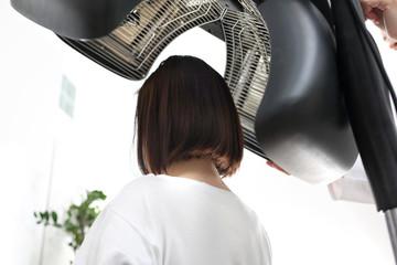 Pielęgnacja włosów . Kobieta podczas zabiegu pielęgnacyjnego na włosy w salonie fryzjerskim.