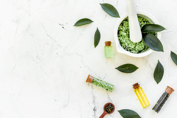 Make cosmetics with tea tree essential oil. Homemade cosmetics. Fresh tea tree leaves, mortar and pestel, cosmetics on white stone background top view border copy space