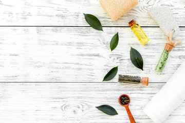 Tea tree spa composition. Fresh tea tree leaves, natural cosmetics, towel on white wooden background top view space for text border